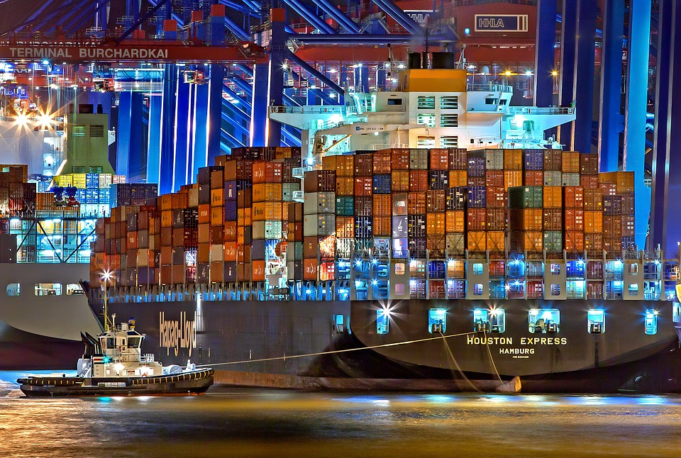 A ship with shipping containers at night.
