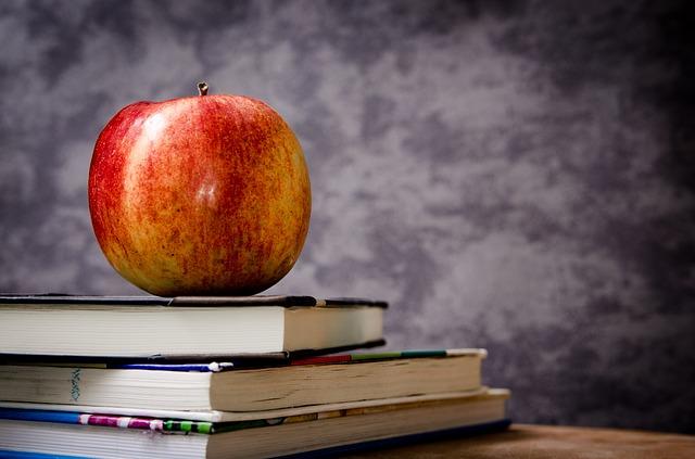 An apple on books.