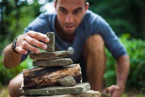man stacking stones