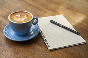 A coffee and a notebook to write how to pack your household in a week
