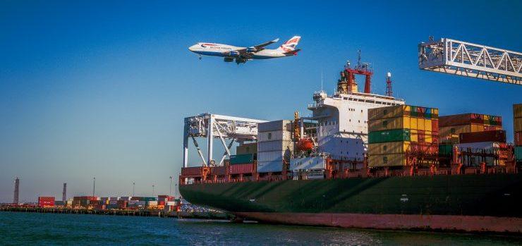 Plane flying over a cargo ship.