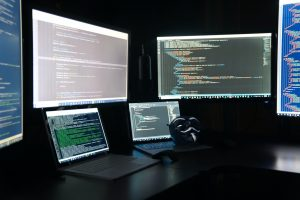 A computer work station featuring 2 laptops and multiple monitors of computer code with an anonymous (Anon) Guy Fawkes mask laying on one of the laptops.
