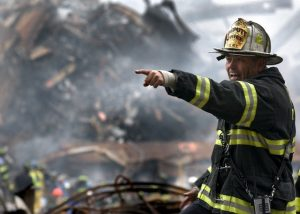 Firefighter in front of a pile of rubbish
