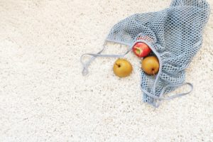 Apples fell out of a grocery bag on a beige carpet