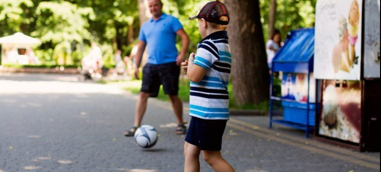 Boy and man playing soccer