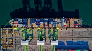 A port with a ship on the dock full of containers