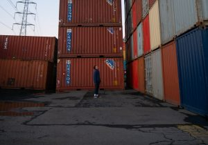 A person in front of the containers