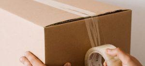 Taping a cardboard box.
