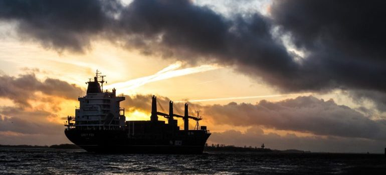A freighter transporting boats and yahts in the sunset