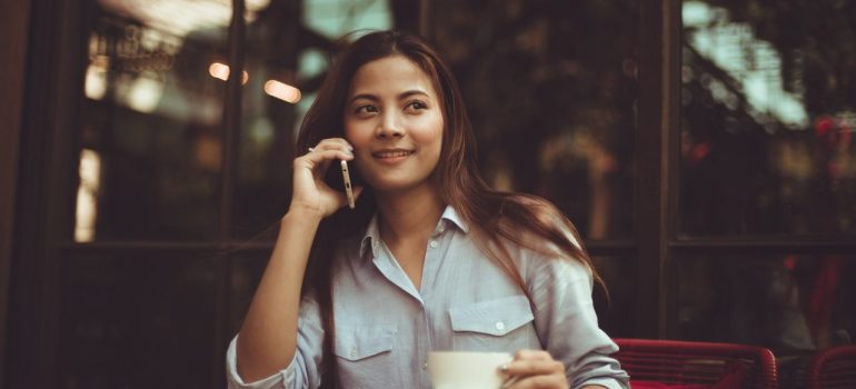 a woman drinking coffee in a coffee shop while talking on the phone