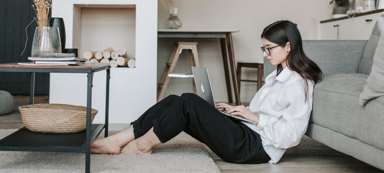 A woman sitting on the floor using laptop