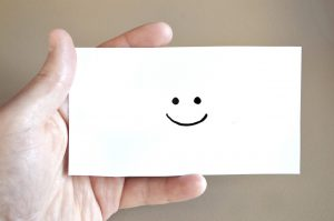 a hand holding a smiling card as a way to identify a good freight forwarder