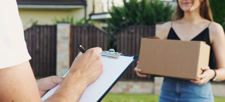 a man delivering a package to a girl and writing it down