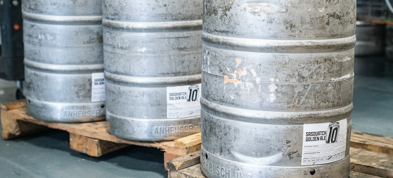 Three metal barrels on wooden pallete