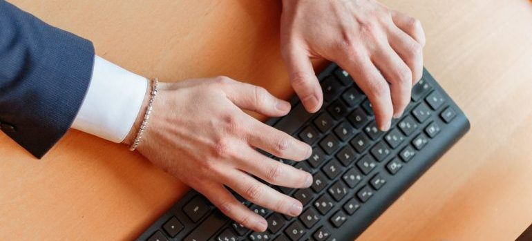 A man typing on an office keyboard.