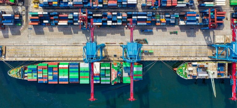 a birds eye view of a shipping port with a ship loading containers on it