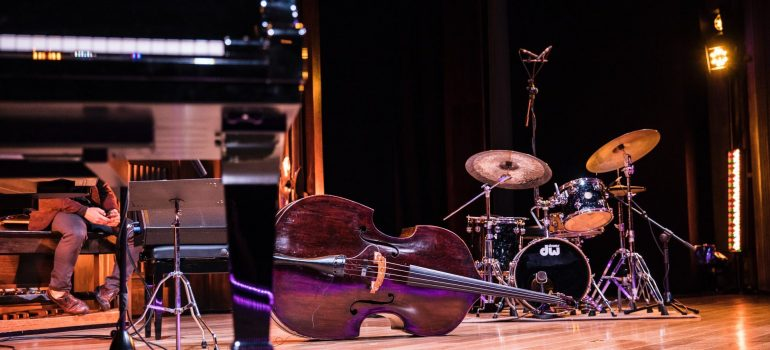 a black piano in front of a drum kit and a cello