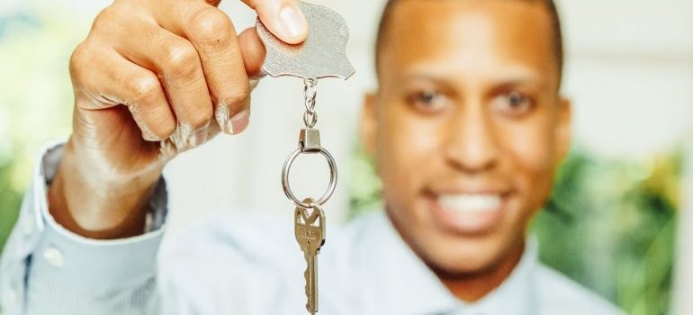Man holding a silver key which is focused.