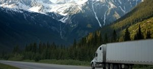a white truck on the road beneath the mountains as a part of the cold chain logistics in flower delivery