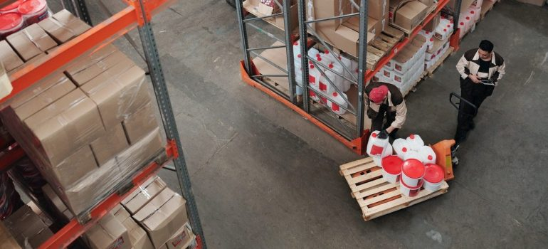 two workers loading items on a pallet after learning that a warehouse can sustain your product