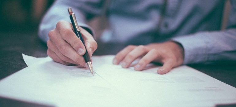 Man noting down on paper things to know before moving overseas