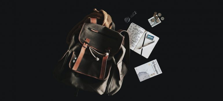 a backpack with items around it as a representation of what you should pack in your hand luggage