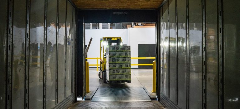 a forklift placing a stack of items inside a chamber