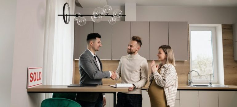 Realtor shaking hands with the couple to whom he just sold a house.