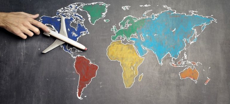 a model airplane on a drawn map of the world showing how air freight packaging requirements have changed