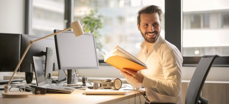 Man holding a book in front of his desk researching online startups in KSA