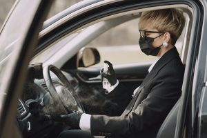 Woman in formal clothes disinfecting steering wheel