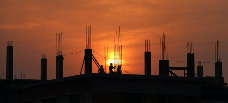 Silhouette of men in construction site during sunset
