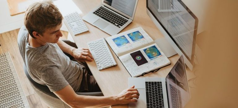 A man using 3 computers and researching trending topics in the cold chain industry