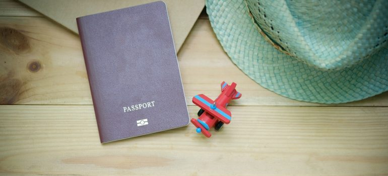 Red passport on the table with red airplane toy and blue hat.