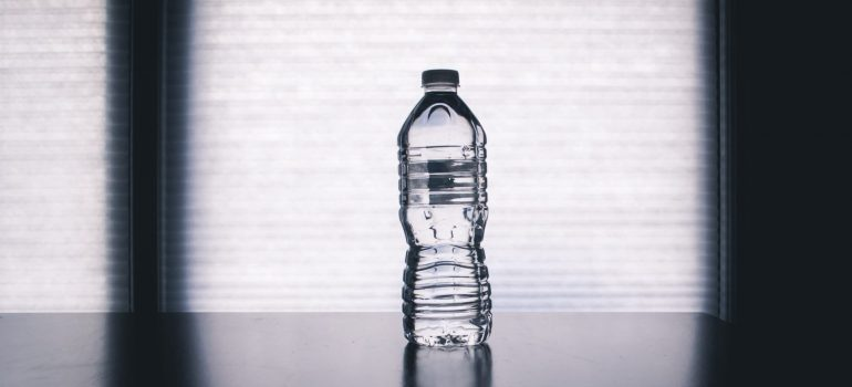 a bottle of water on the table in a dark room
