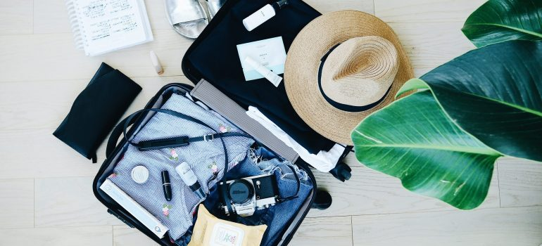 an open suitcase packed with clothes, beauty products, a camera and a hat