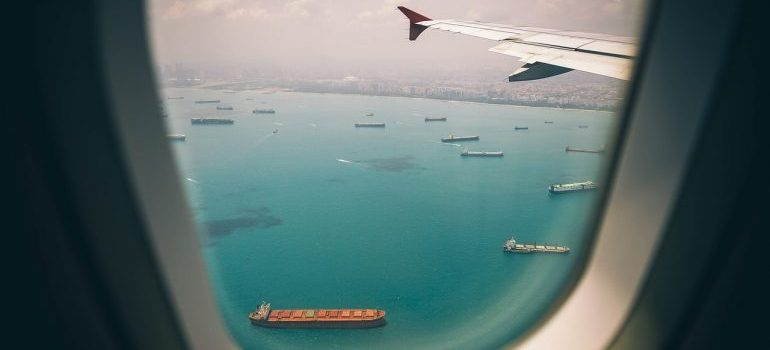 A look through an airplane window on ships in the sea