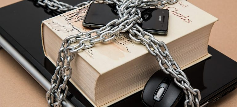 a laptop, a book and a cellphone tied with a chain representing items you cannot bring with you when moving to KSA in 2021