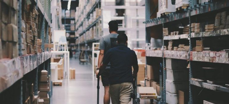 two men walking among the warehouse shelves and boxes