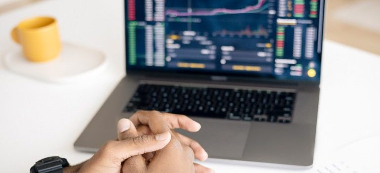 Man sitting in front of a laptop watching the stock market