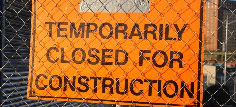 Construction warning sign on a fence