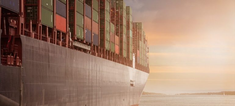 a large ship carrying containers across the sea representing supply chain disruptions in 2021
