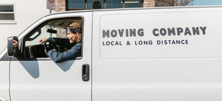 a man sitting inside a white moving van