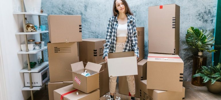 a woman holding a cardboard box with packing peanuts inside it to prevent moving day disasters
