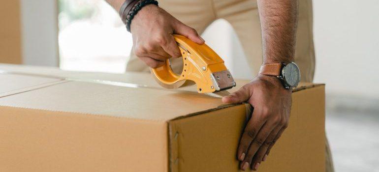 Person tapping shut a cardboard box