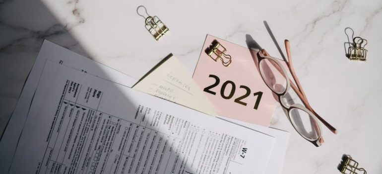 Business calender next to a pair of glasses on a marble table