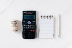 A stack of money, calculator, notepad, and pen