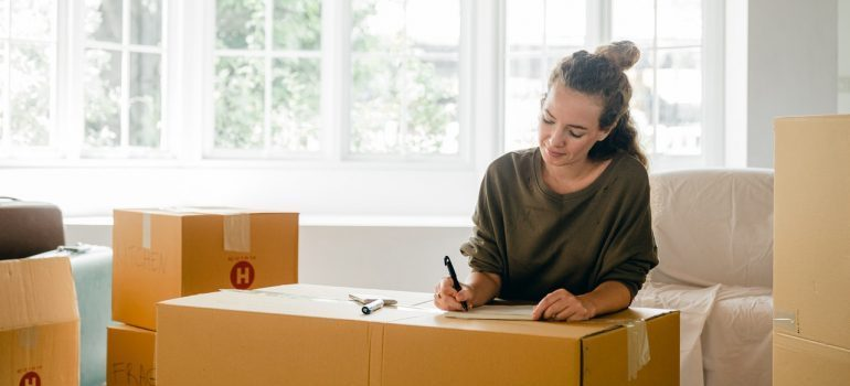Woman labeling a cardboard moving box