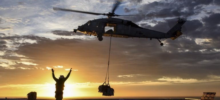 Helicopter picking up cargo during a sunset