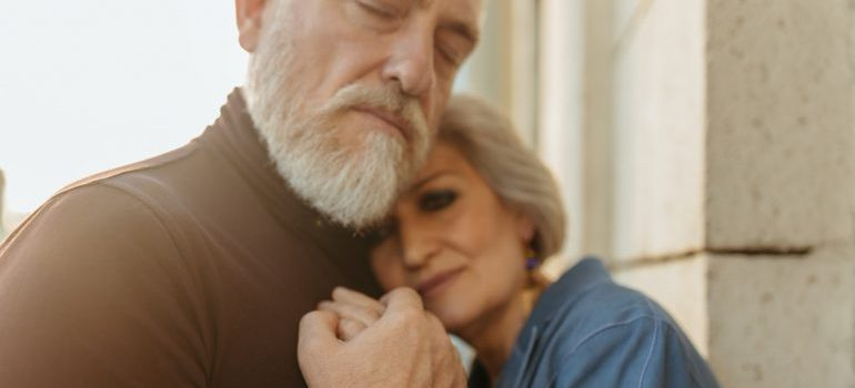 Elderly couple holding hands while hugging